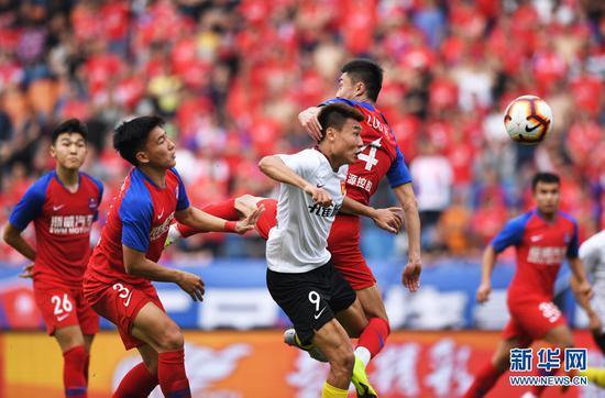 4月13日,河北华夏幸福队球员董学升(中)在比赛中拼抢。新华社记者王全超摄