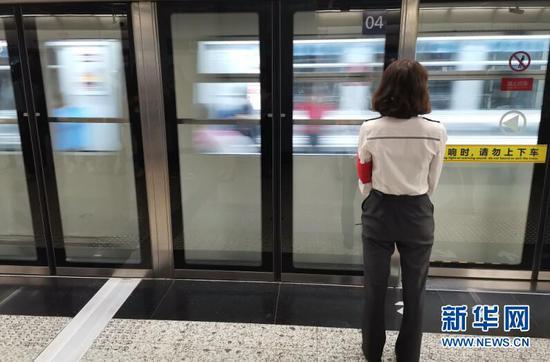 图为重庆轨道交通3号线嘉州路站内,穿着制服的轨道工作人员正在等待列车到站,以引导乘客有序上下车。新华网 韩梦霖 摄