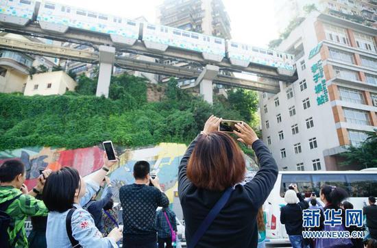 图为游客在轨道李子坝站外的观景平台拍照留影。新华网 韩梦霖 摄
