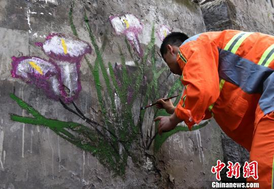 图为环卫工人正在作画美化环境。 周毅 摄