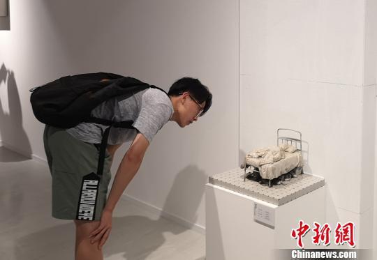 图为观众观看小尺度具象雕塑作品。 刘贤 摄