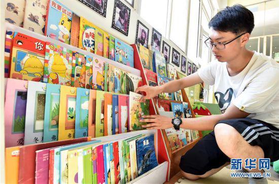 陈叙良为小朋友们整理图书(9月4日摄)。新华社发(庄文斌 摄)