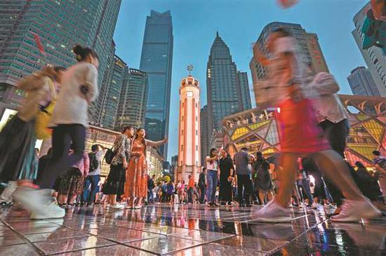 游客纷纷与重庆地标-解放碑合影留念。