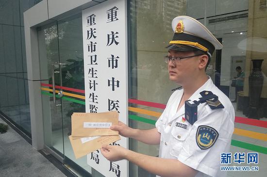 重庆市卫生计生监督执法局的执法人员出发前开启装有被监督单位名单的信封。新华网 韩梦霖 摄