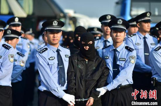 资料图为重庆警方押解电信网络诈骗犯罪嫌疑人。 重庆市公安局供图