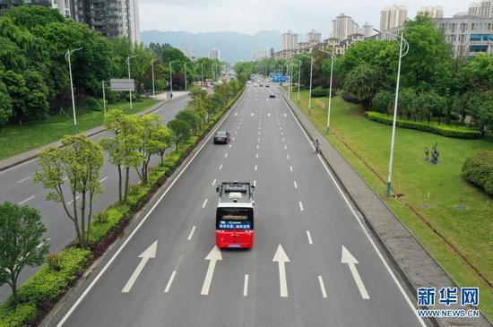 4月12日,自动驾驶公交车在永川城区内行驶(无人机照片)。