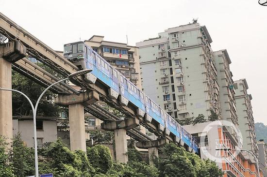 轨道2号线经过李子坝站从8层楼中间穿越驶过。