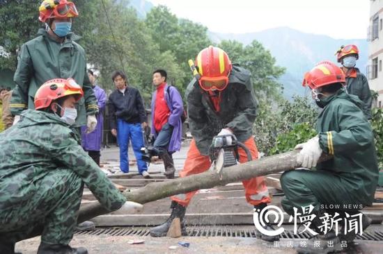 △在东汽中学救援可乐男孩现场,谭明华(左,拿着木棒)与战友做支撑材料