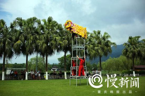 """谢凤国和徒弟王华彪在四层八仙桌上表演重庆市非物质文化遗产项目""""双桥狮舞"""""""