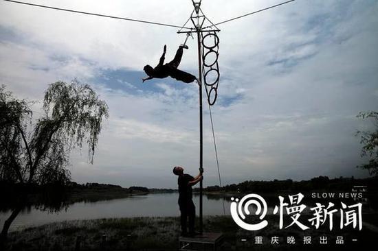 """谢凤国和徒弟王华彪在7米高杆上表演百年""""双桥高杆""""杂技"""