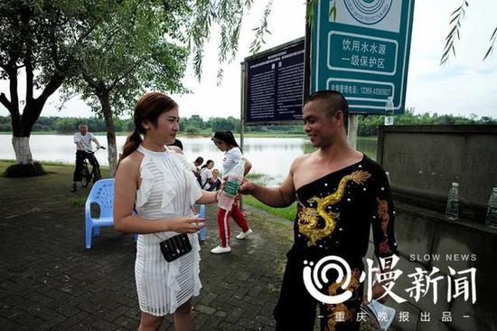 妻子杨玉婷为满头大汗的谢凤国送上冰冻矿泉水降温解渴