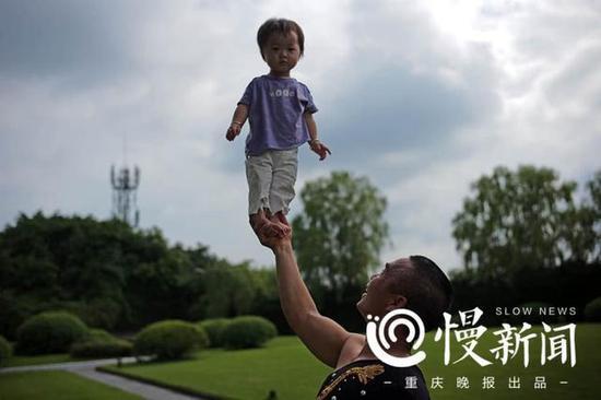 谢凤国单手将小孩托举,练习臂力