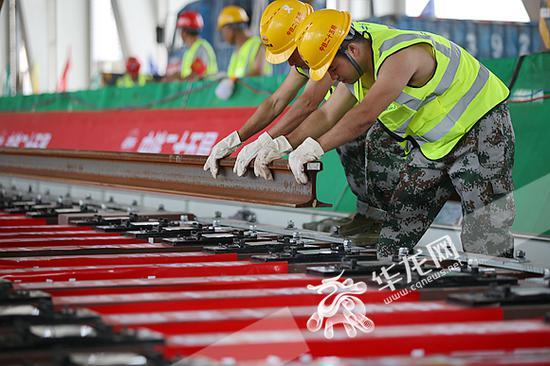 工人将吊装的轨道装入指定位置。记者 李裕锟 摄