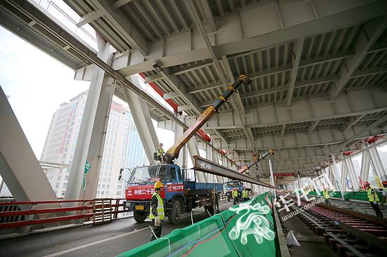 铁轨从旁边公路吊装进轨道位置。记者 李裕锟 摄