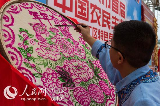 1名民间艺人在黔江区武陵文化广场绘画丰收图。
