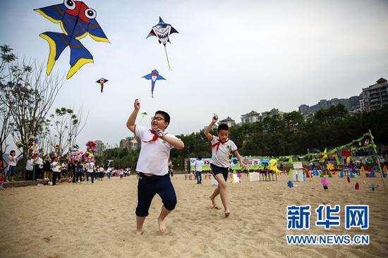 孩子们在阳光沙滩放风筝。新华网发(刘兴敏 摄)