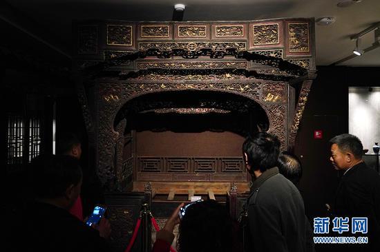 市民参观永川博物馆馆藏的清代镂空高浮雕花草瑞兽拔步床。新华网 李相博 摄