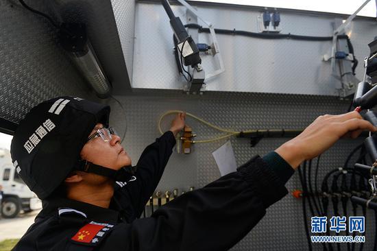 工作人员在中型应急通信车内架设天线。新华网 李相博 摄