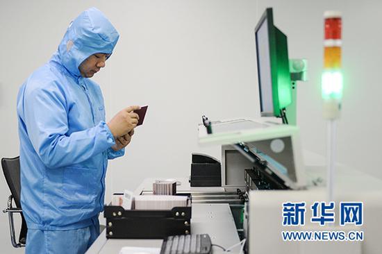 工作人员查看电子护照自动质检机上的证件。新华网发(重庆市公安局出入境管理局供图)