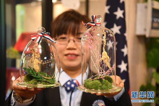 图为重庆保税体验旅游景区内美国馆工作人员展示商品。新华网 陶玉莲 摄