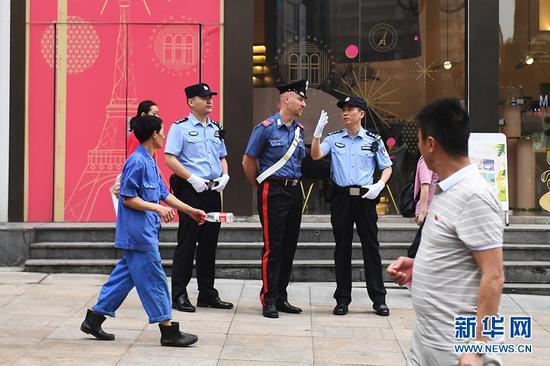 6月27日,中意警员在联合巡逻期间相互交流。新华网 李相博 摄