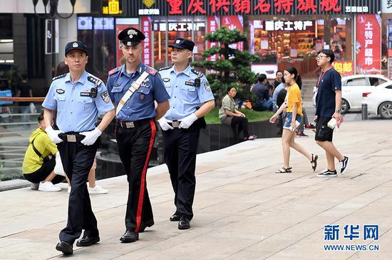 6月27日,中意警员在重庆解放碑进行联合巡逻。新华网 李相博 摄