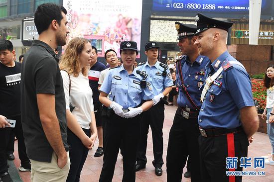 6月27日,中意警员在重庆解放碑为外国游客提供帮助。新华网 李相博 摄