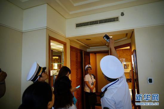执法人员向酒店清洁人员询问空调出风口的清洗状况。新华网 韩梦霖 摄