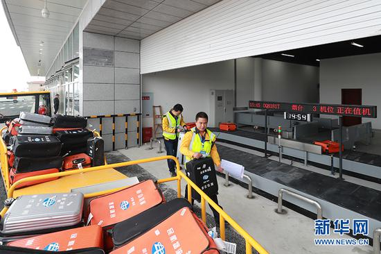 工作人员模拟行李转运环节。新华网发(莫晓健 摄)