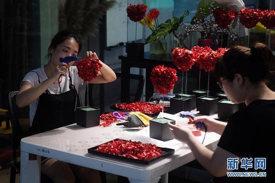商家利用玫瑰花瓣制作桃心状礼盒。新华网 李相博 摄
