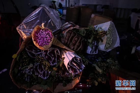 负责送货的师傅,将花束捆扎在摩托车上,即将发往各处商家。新华网 李相博 摄