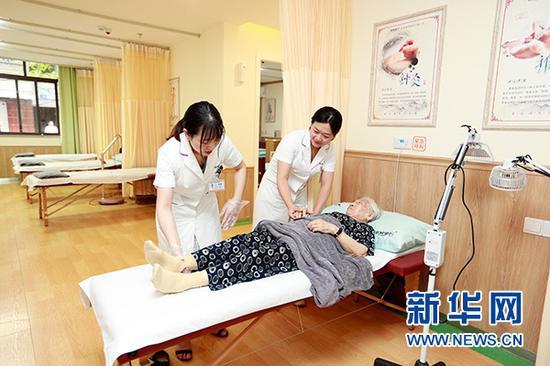 图为重庆市渝北区龙山街道,社区老人在养老服务中心进行康复理疗。新华网发(重庆市民政局供图)