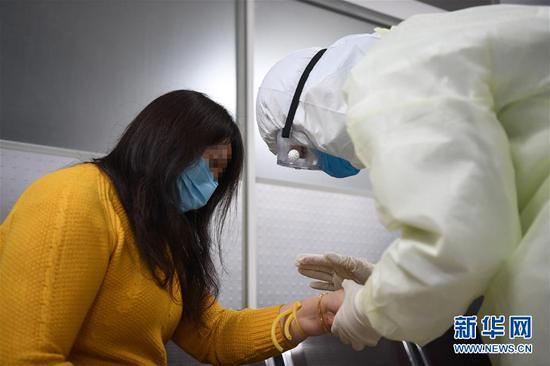 2月17日,新冠肺炎康复患者舒某(左)在做捐献血浆前的准备工作。新华社记者 唐奕 摄