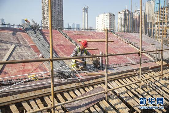 8月28日,工人在重庆十八梯传统风貌改造项目现场施工。新华社记者 黄伟 摄