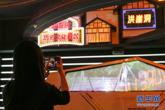 一位参观者正在馆内的重庆历史文化街区前留影。新华网发 耿骏宇 摄