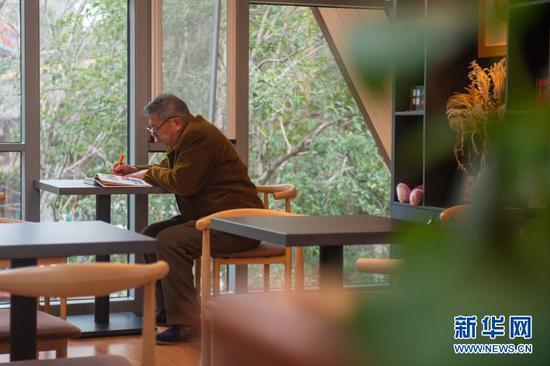 1月5日,在嘉兴市南湖区洪兴路一处城市驿站内,一名老人在阅读书籍。新华社发(江汉 摄)