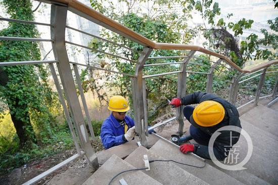 △渝中区半山崖线步道,工作人员正在安装护栏