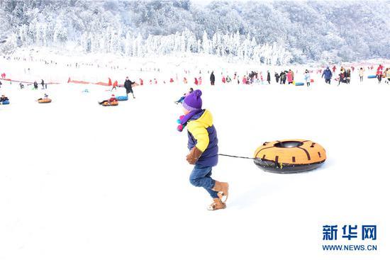 """冷水国际滑雪场的游客在体验""""雪上飞碟""""。新华网发(付光禄 摄)"""