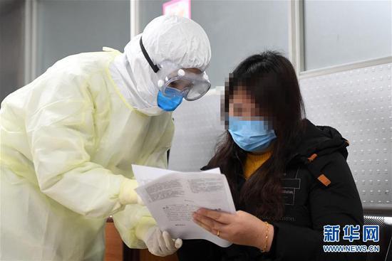 2月17日,新冠肺炎康复患者舒某(右)在做捐献血浆前的准备工作。新华社记者 唐奕 摄