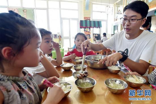 陈叙良正在照顾小朋友们吃午饭,细心引导他们不要挑食(9月4日摄)。 新华社发(庄文斌 摄)