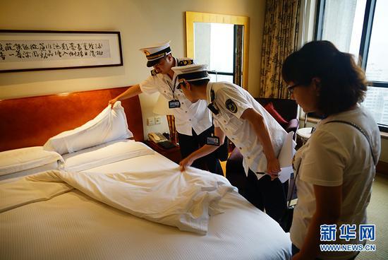 执法人员在突击检查希尔顿酒店客房的床单卫生情况。新华网 韩梦霖 摄