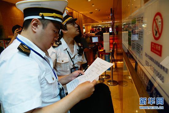 执法人员在检查酒店前台的卫生许可证等公示信息。新华网 韩梦霖 摄