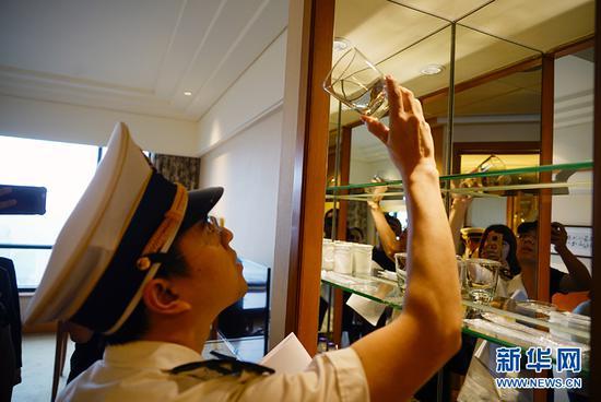 执法人员在仔细检查酒店客房里水杯的卫生清洁情况。新华网 韩梦霖 摄