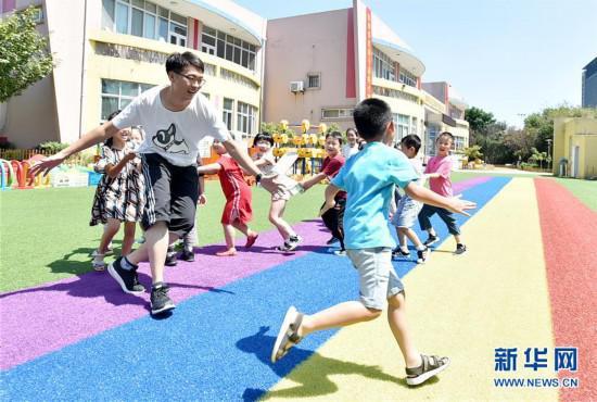 陈叙良跟小朋友们玩老鹰捉小鸡的游戏(9月4日摄)。新华社发(庄文斌 摄)