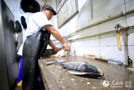 一条鲜活的鱼,制作成为万州烤鱼需要经过多个环节。何超 摄