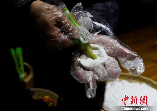图为工作人员为食客包芥末汤圆煮火锅。 周毅 摄