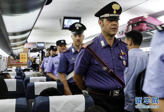 7月2日,中意警员在一列动车组车厢内进行巡逻。新华网发(张免 摄)