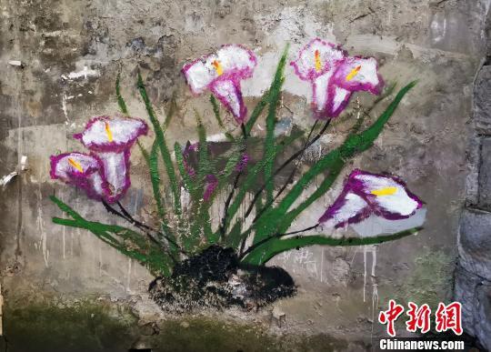 """图为环卫工人在铲掉""""牛皮癣""""的墙壁上作画美化环境。 周毅 摄"""