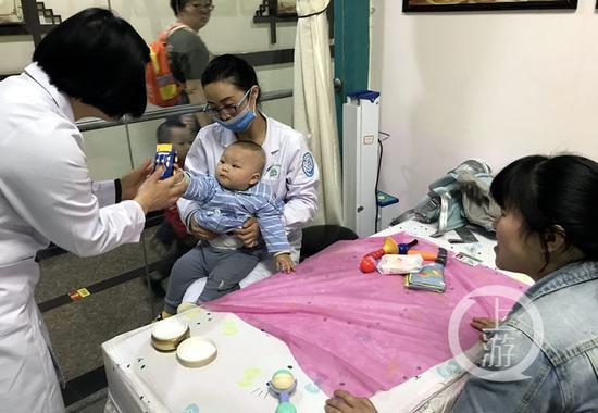 △一个医生给小孩做按摩治疗,另一个医生拿玩具逗孩子玩,以免哭闹。