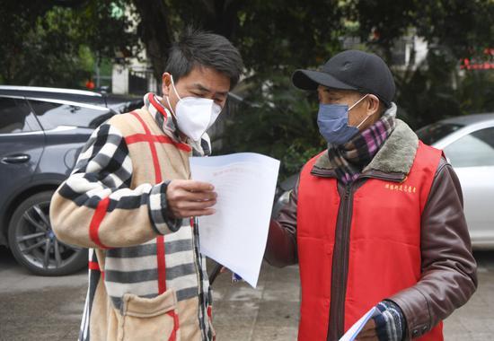 2月3日,重庆市万州区牌楼街道石峰社区志愿者(右)向居民发送疫情防控宣传资料。新华社记者王全超摄